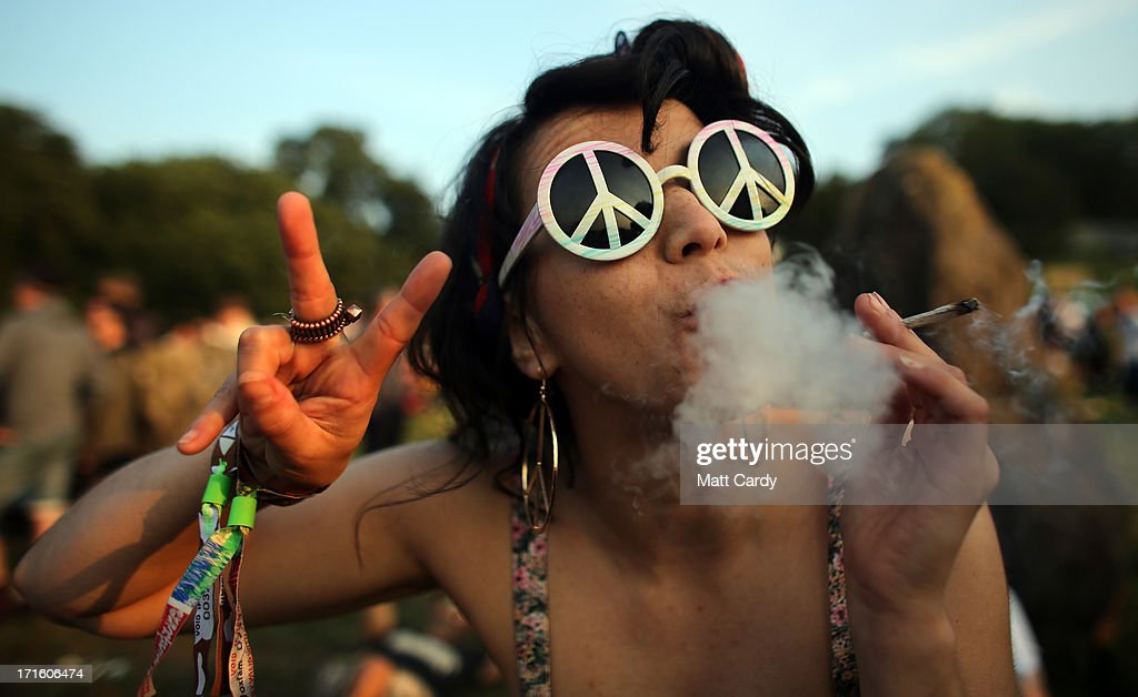 Rudina Hatipi smokes as she joins fellow revellers as they gather for the sunset at the stone circle at the Glastonbury Festival of Contemporary Performing Arts site at Worthy Farm, Pilton on June 26, 2013 near Glastonbury, England. Gates opened today at the Somerset diary farm that will be playing host to one of the largest music festivals in the world and this year features headline acts Artic Monkeys, Mumford and Sons and the Rolling Stones. Tickets to the event which is now in its 43rd year sold out in minutes and that was before any of the headline acts had been confirmed. The festival, which started in 1970 when several hundred hippies paid 1 GBP to watch Marc Bolan, now attracts more than 175,000 people over five days.