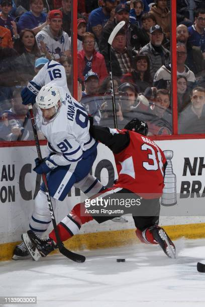 Rudolfs Balcers of the Ottawa Senators battles for puck possession against John Tavares of the Toronto Maple Leafs at Canadian Tire Centre on March...
