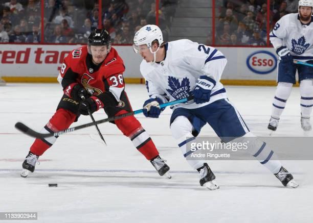 Rudolfs Balcers of the Ottawa Senators lifts the stick of Kasperi Kapanen of the Toronto Maple Leafs as he backchecks at Canadian Tire Centre on...