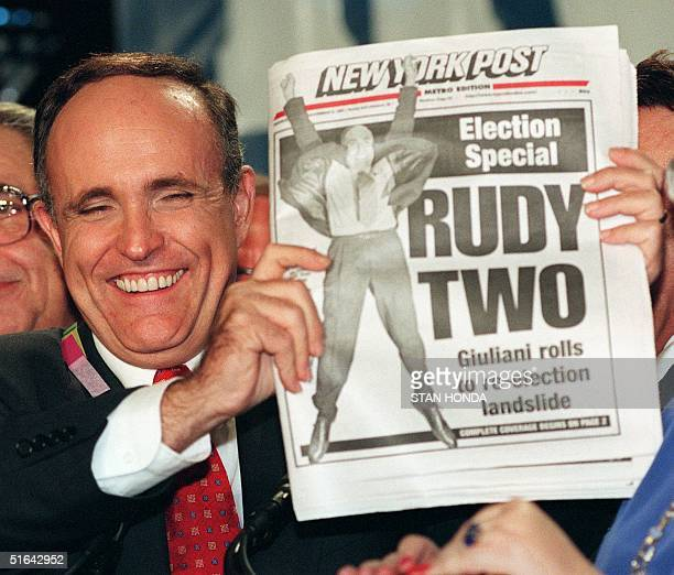 Rudolph W. Giuliani celebrates his re-election as mayor of New York City 04 November by holding up an early copy of the New York Post newspaper in...