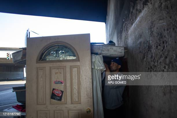 Rudy Campos 43 yearsold fixes a curtain in the entrance of his tent under the bridge of the 110 Freeway at 39th Street during the novel Coronavirus...