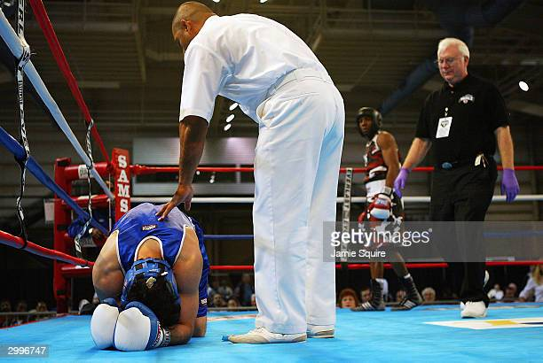 Rudy Cisneros is attended to by the referee and Dr Charles Butler after being knocked down by Edward Joseph in the United States Olympic Team Boxing...