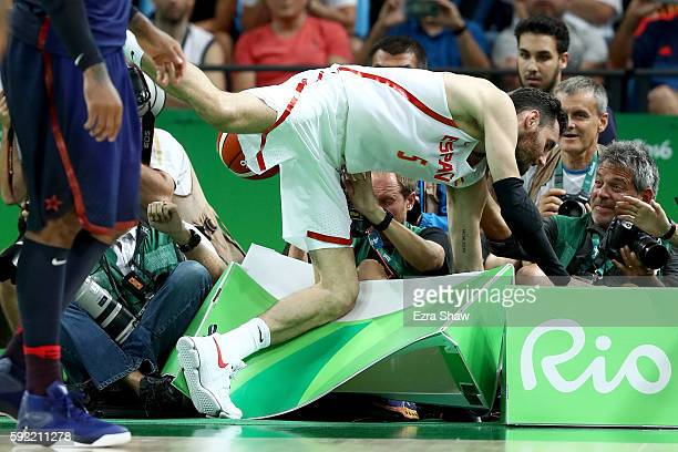 Rudy Fernandez of Spain falls into the photographer's row during the Men's Semifinal match against the United States on Day 14 of the Rio 2016...