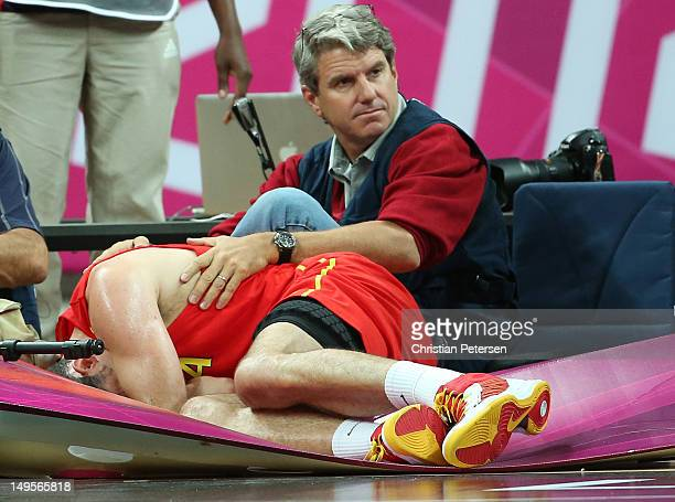 Rudy Fernandez of Spain lands heavily on Reuters photographer Mike Segar in the Men's Basketball Preliminary Round match between Australia and Spain...