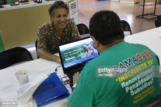Rudy Figueroa , an insurance agent from Sunshine Life and Health Advisors, speaks with Marvin Mojica as he shops for insurance under the Affordable...