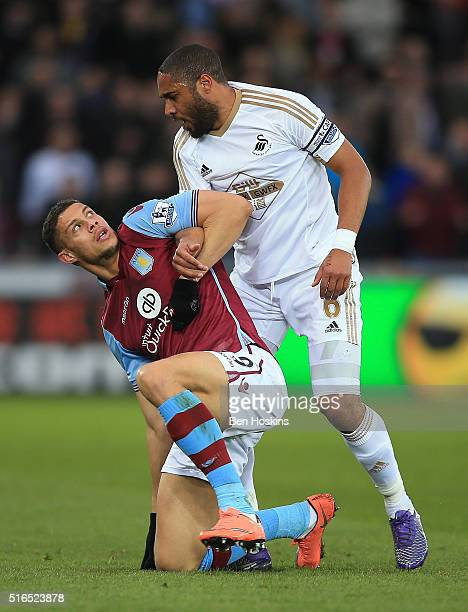 Rudy Gestede of Aston Villa and Ashley Williams of Swansea City face off during the Barclays Premier League match between Swansea City and Aston...