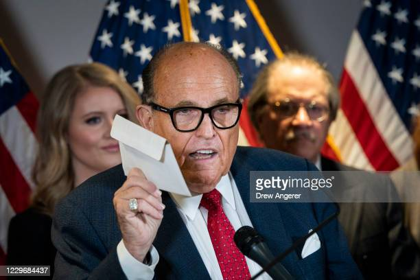Rudy Giuliani holds up a mail-in ballot as he speaks to the press about various lawsuits related to the 2020 election, inside the Republican National...