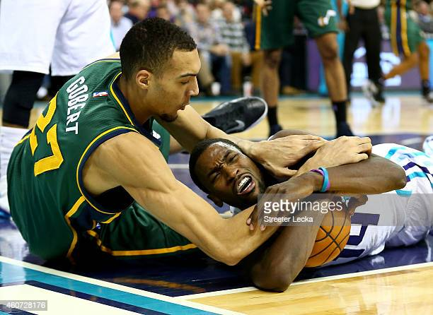 Rudy Gobert of the Utah Jazz and Michael KiddGilchrist of the Charlotte Hornets battle for a loose ball during their game at Time Warner Cable Arena...