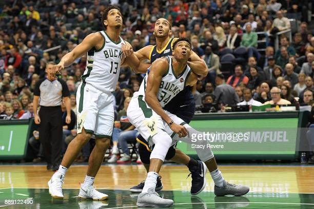 Rudy Gobert of the Utah Jazz is blocked out by Malcolm Brogdon and Giannis Antetokounmpo of the Milwaukee Bucks during the first half of a game at...