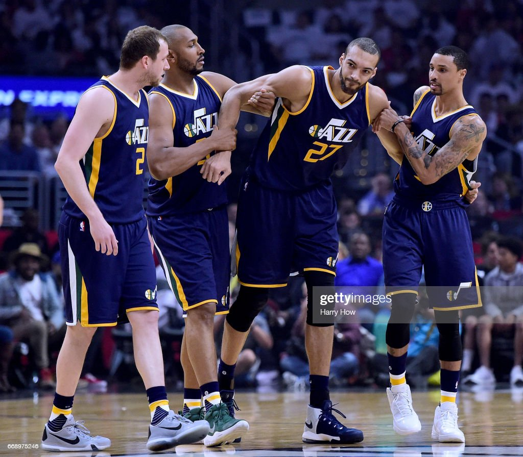 Rudy Gobert #27 of the Utah Jazz is helped off the court by Joe Ingles #2, Boris Diaw #33 and George Hill #3 after an injury during the first half against the LA Clippers at Staples Center on April 15, 2017 in Los Angeles, California.