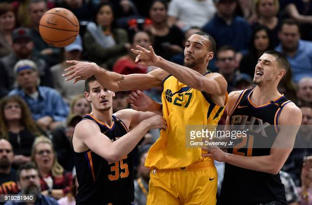 Rudy Gobert of the Utah Jazz passes the ball between defenders Dragan Bender and Alex Len of the Phoenix Suns during a game at Vivint Smart Home...