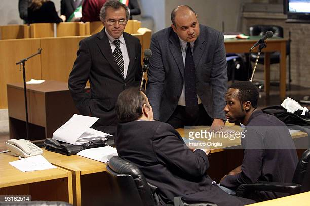 Rudy Guede who was born in the Ivory Coast chats with his lawyers in the Perugia courthouse during the sitting of his appeal against the sentence he...