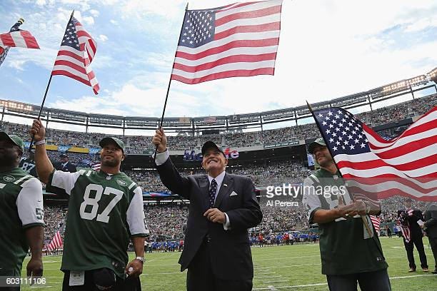 Rudy Guliani waves an American Flag flanked by former New York Jets players Marvin Jones, Laveranues Coles and Wayne Chrebet when he serves as...