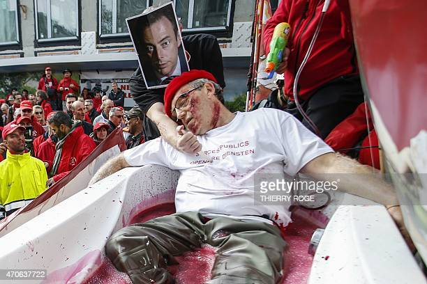 Rudy Janssens, secretary of ACOD-LRB/CGSP-ALR union, takes part, with an activist wearing as a mask a portrait of Bart De Wever, head of the New...