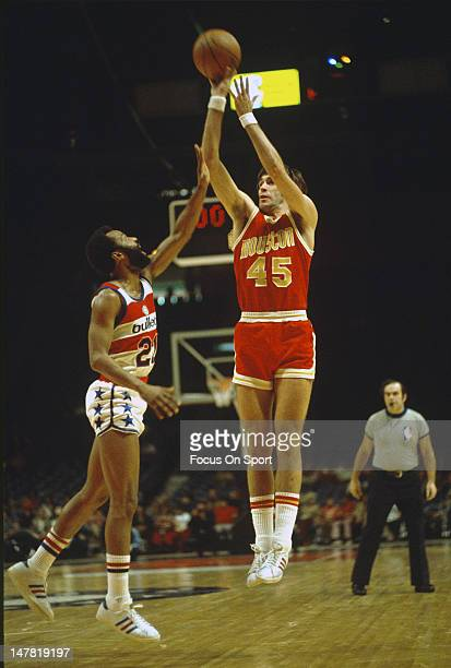 Rudy Tomjanovich of the Houston Rockets looks to shoot over Archie Clark of the Baltimore Bullets during an NBA basketball game circa 1973 at the...