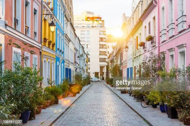rue cremieux multicolored street during sunrise without people in paris, france - street stockfoto's en -beelden