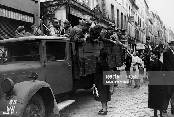 Rue Lepic in Montmartre Parisians are giving food to French war prisoners gathered in a lorry of the Wehrmacht