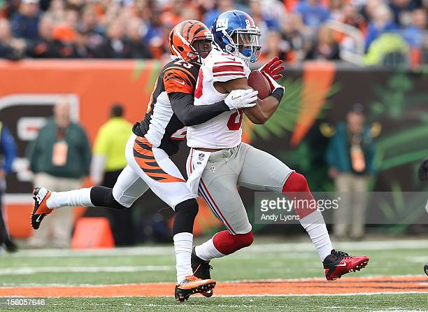 Rueben Randle of the New York Giants is hit as he catches the ball by Terence Newman of the Cincinnati Bengals during the game at Paul Brown Stadium...