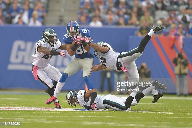 Rueben Randle of the New York Giants is hit by Earl Wolff and Mychal Kendricks of the Philadelphia Eagles over a fallen Bradley Fletcher at MetLife...