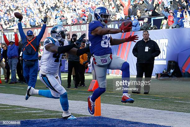 Rueben Randle of the New York Giants scores a 27 yard touchdown in the first quarter against Roman Harper of the Carolina Panthers during their game...