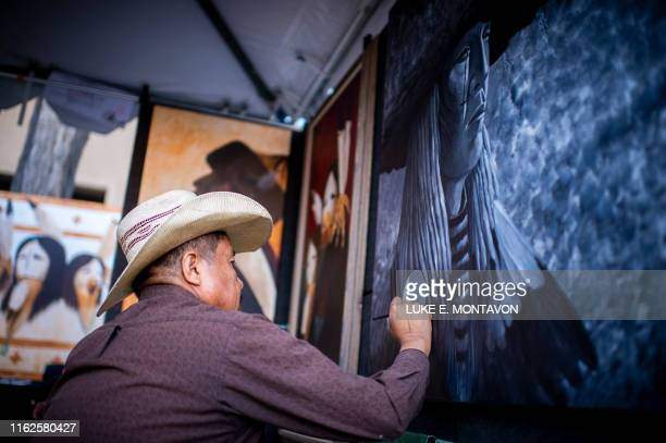 Rueben Richards of Dennehotso Arizona works on his art while waiting for patrons to come during the 98th annual Santa Fe Indian Market the largest...