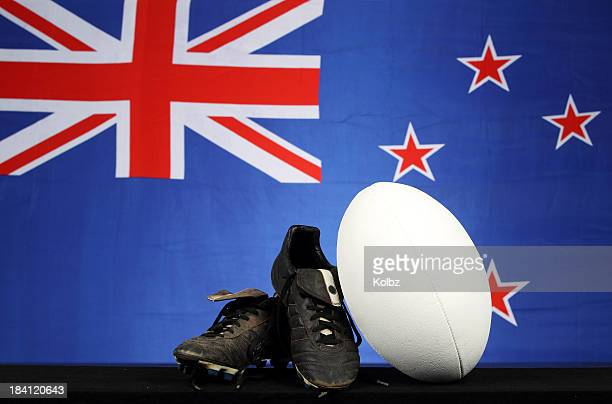 rugby ball and shoes in front of new zealand flag backdrop - ankle boot stock pictures, royalty-free photos & images