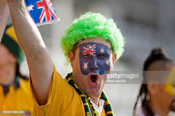 Rugby fan with Australian flag painted on face, shouting