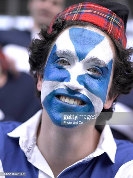 Rugby fan with Scottish flag painted on face, smiling, portrait, close-up
