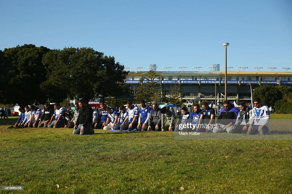 Rugby league supporters stop to pray outside the ground as they crowd arrives for the round 20 NRL match between the Canterbury Bulldogs and the Cronulla Sharks at Belmore Sports Ground on July 26, 2015 in Sydney, Australia.