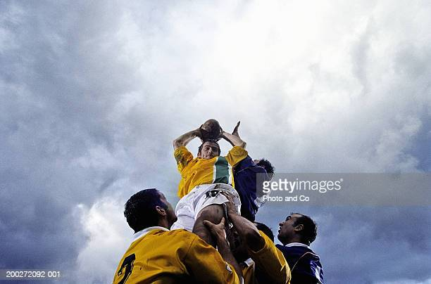 Rugby lineout jumper being supported by team-mates, low angle view