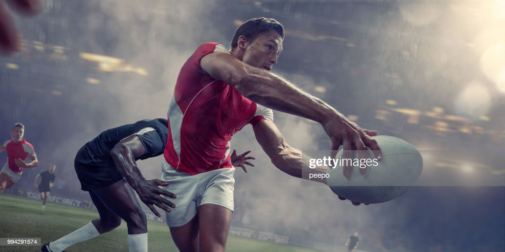 Rugby Player About To Pass Ball Just Before Being Tackled : Stock Photo