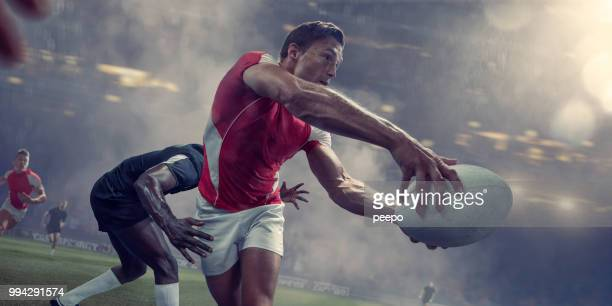 rugby player about to pass ball just before being tackled - passing sport imagens e fotografias de stock