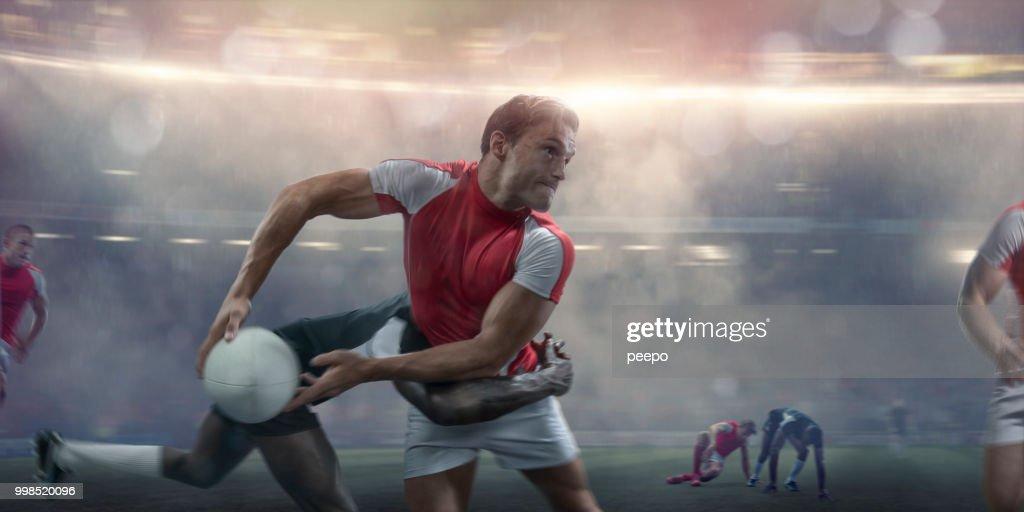 Giocatore di rugby che sta per passare mentre viene affrontato durante la partita : Foto stock
