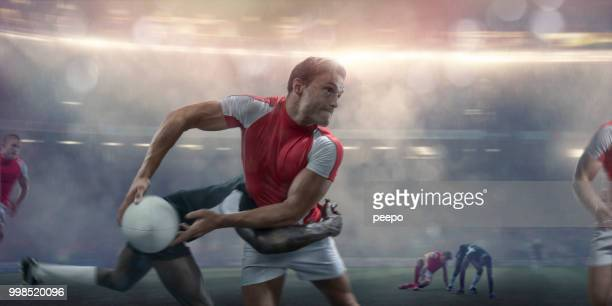 rugby player about to pass whilst being tackled during match - passing sport imagens e fotografias de stock