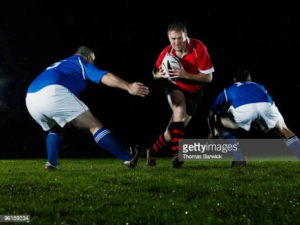 Rugby player avoiding opposing team