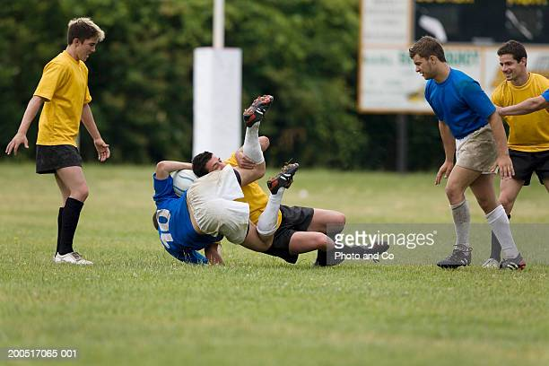Rugby player being tackled on pitch