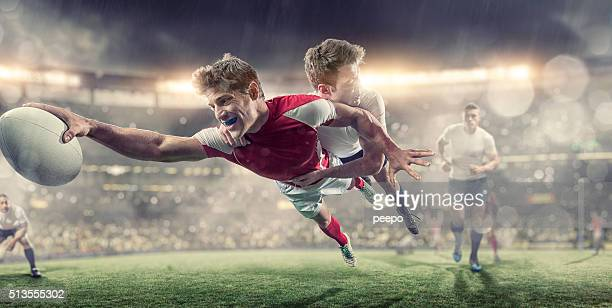rugby player diving to score during tackle in rugby game - rugby union stock pictures, royalty-free photos & images