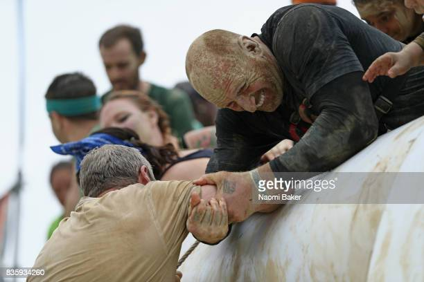 Rugby Player Gareth Thomas helps fellow competitors during the 2017 Tough Mudder South West at Badminton Estate on August 20 2017 in Cirencester...