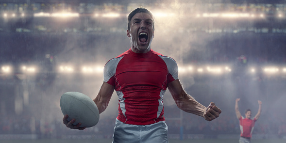 Rugby Player Holding Ball and Shouting in Victory Celebration 1001472500