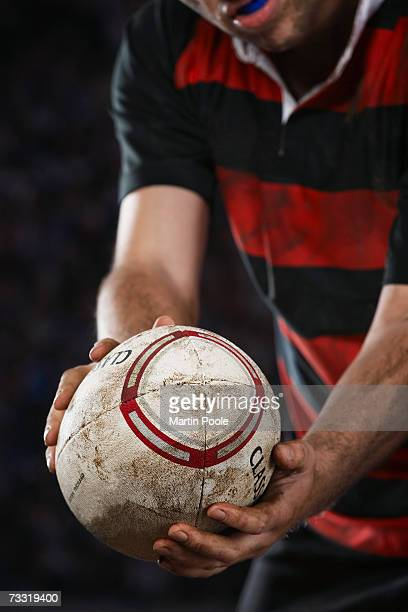 rugby player holding ball, mid section, close up - rugby ball stock pictures, royalty-free photos & images