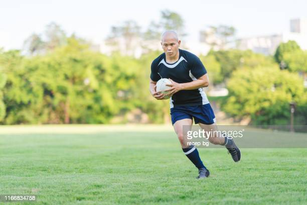 rugby player holding rugby ball and running - rugby league stock pictures, royalty-free photos & images