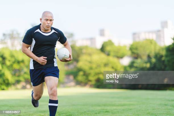 rugby player holding rugby ball and running - rugby union stock pictures, royalty-free photos & images