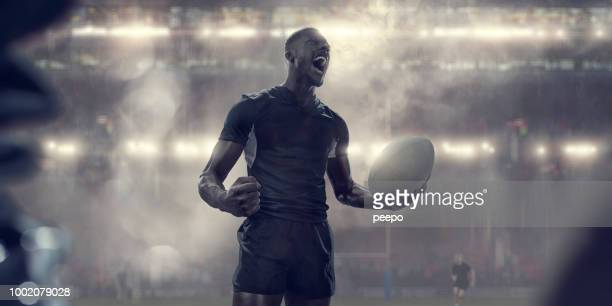 rugby player in black kit holding ball shouting in celebration - rugby union imagens e fotografias de stock