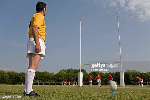 Rugby player in field preparing to kick ball from tee, side view