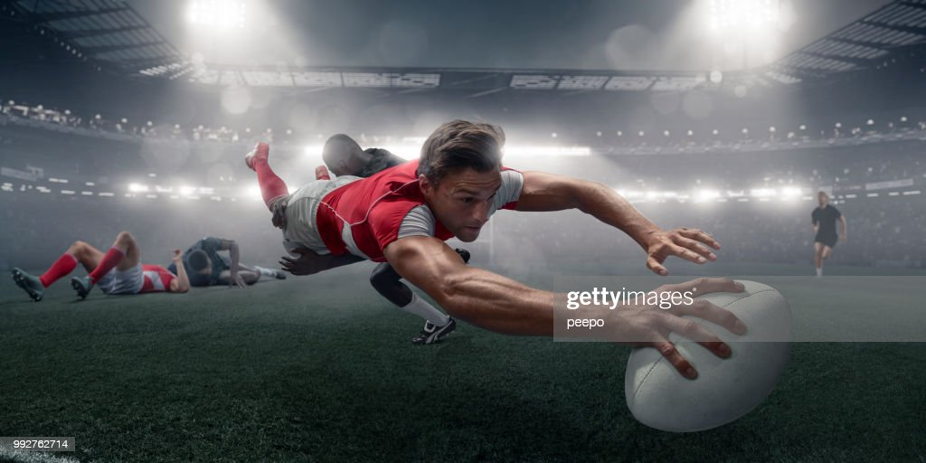 Rugby Player In Mid Air Dive With Ball To Score : Stock Photo