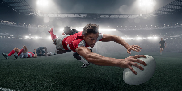 Rugby Player In Mid Air Dive With Ball To Score 992762714
