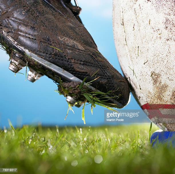 Rugby player kicking ball off tee, close up of foot