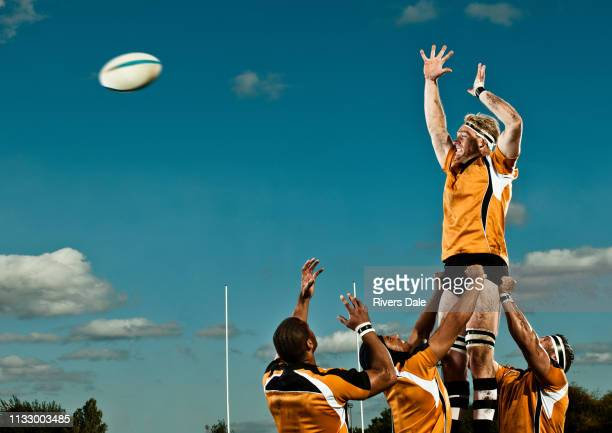 rugby player leaping up to catch ball - rugby stock-fotos und bilder