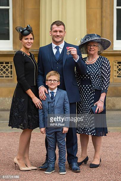 Rugby player Mark Cueto with wife Suzie son Max and mother Anne as he holds his Member of the British Empire medal which was awarded by the Duke of...