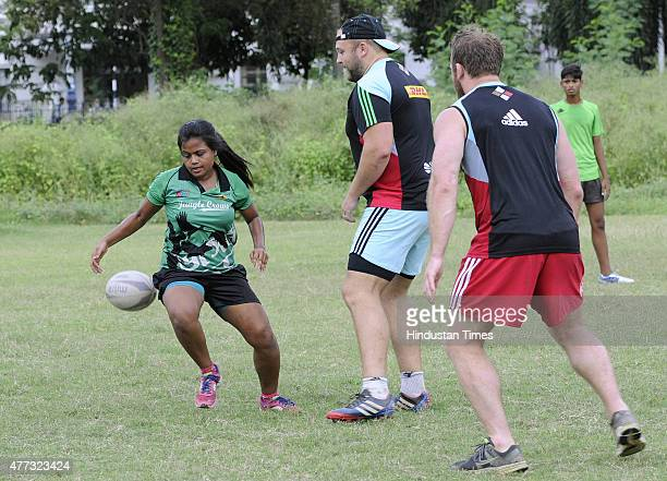 Rugby player of English Rugby club Harlequin Football Club Mark Lambert playing with under privileged children of an NGO to promote the game at...